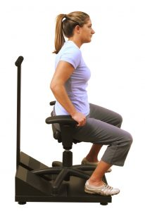 A woman using the Pettibon System Vibration Platform and Wobble Chair for back treatment
